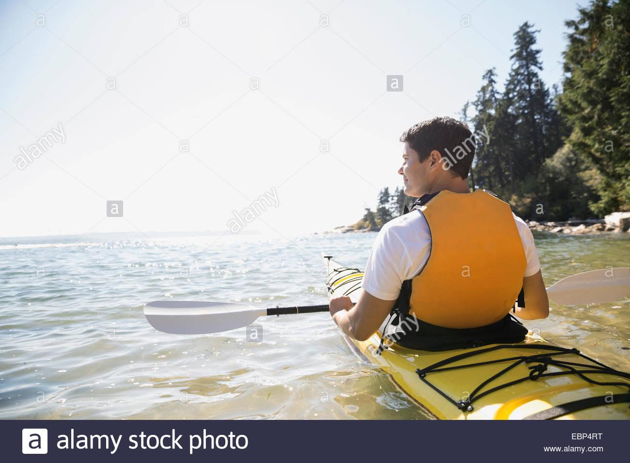 L'uomo kayak sul mare soleggiato Immagini Stock