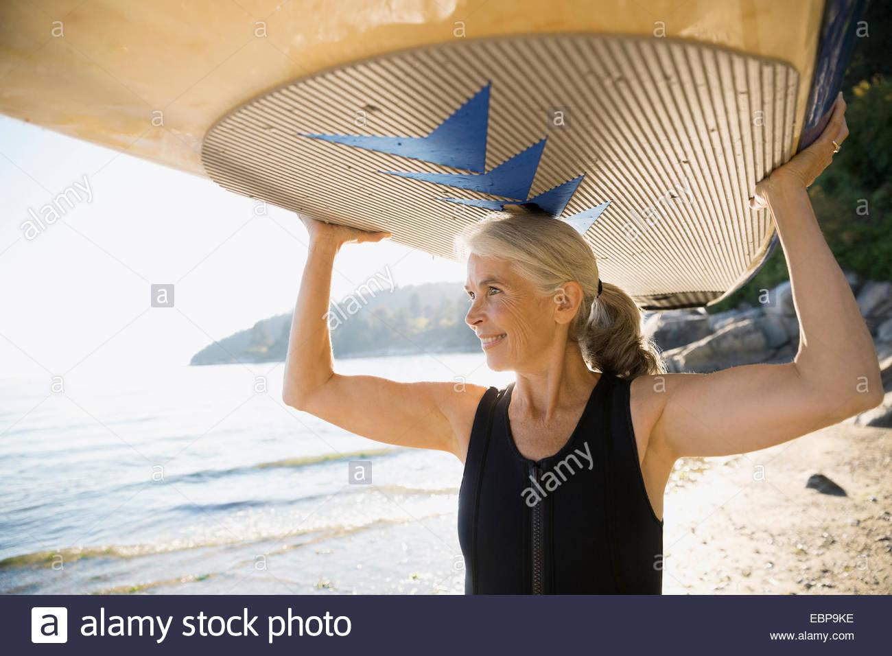 Senior donna holding paddle board overhead sulla spiaggia Immagini Stock