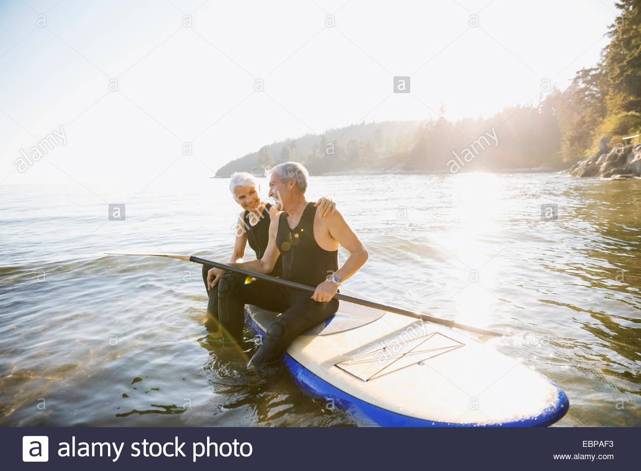 Coppia senior sulla scheda di racchetta in ocean Immagini Stock