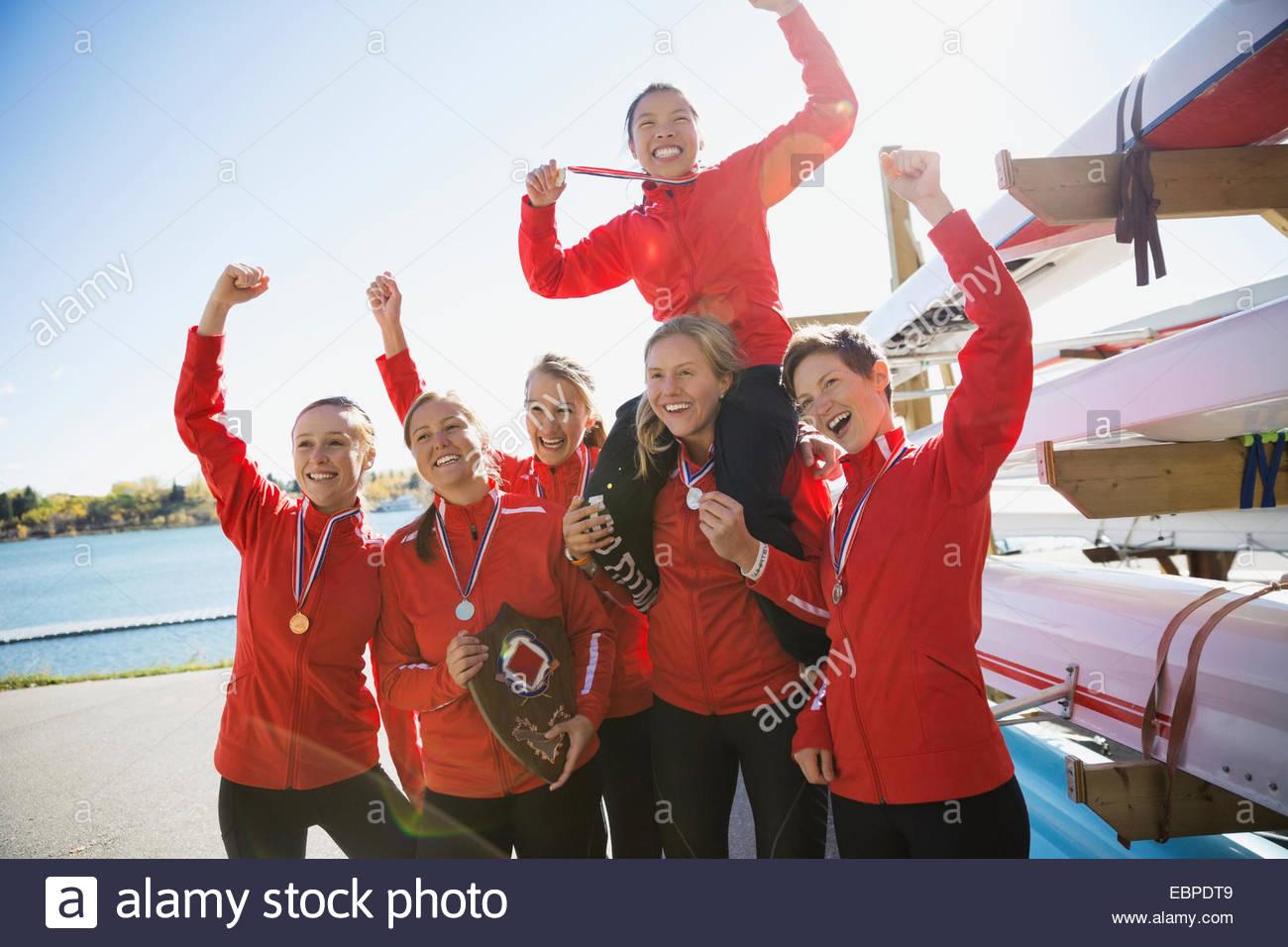 Il team di canottaggio con medaglie celebra vicino skiff Immagini Stock
