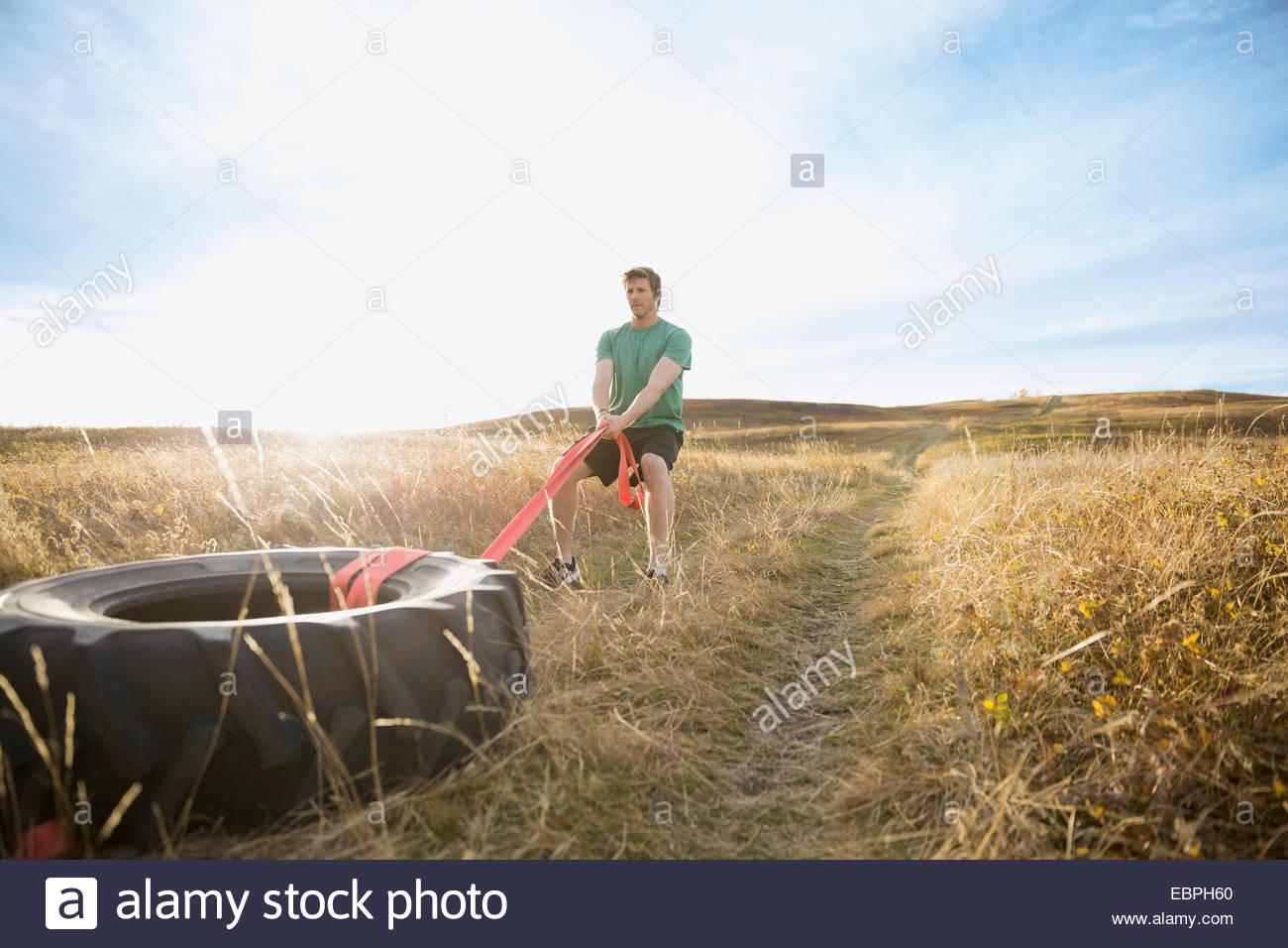 L'uomo tirando crossfit pneumatico nel soleggiato campo rurale Immagini Stock