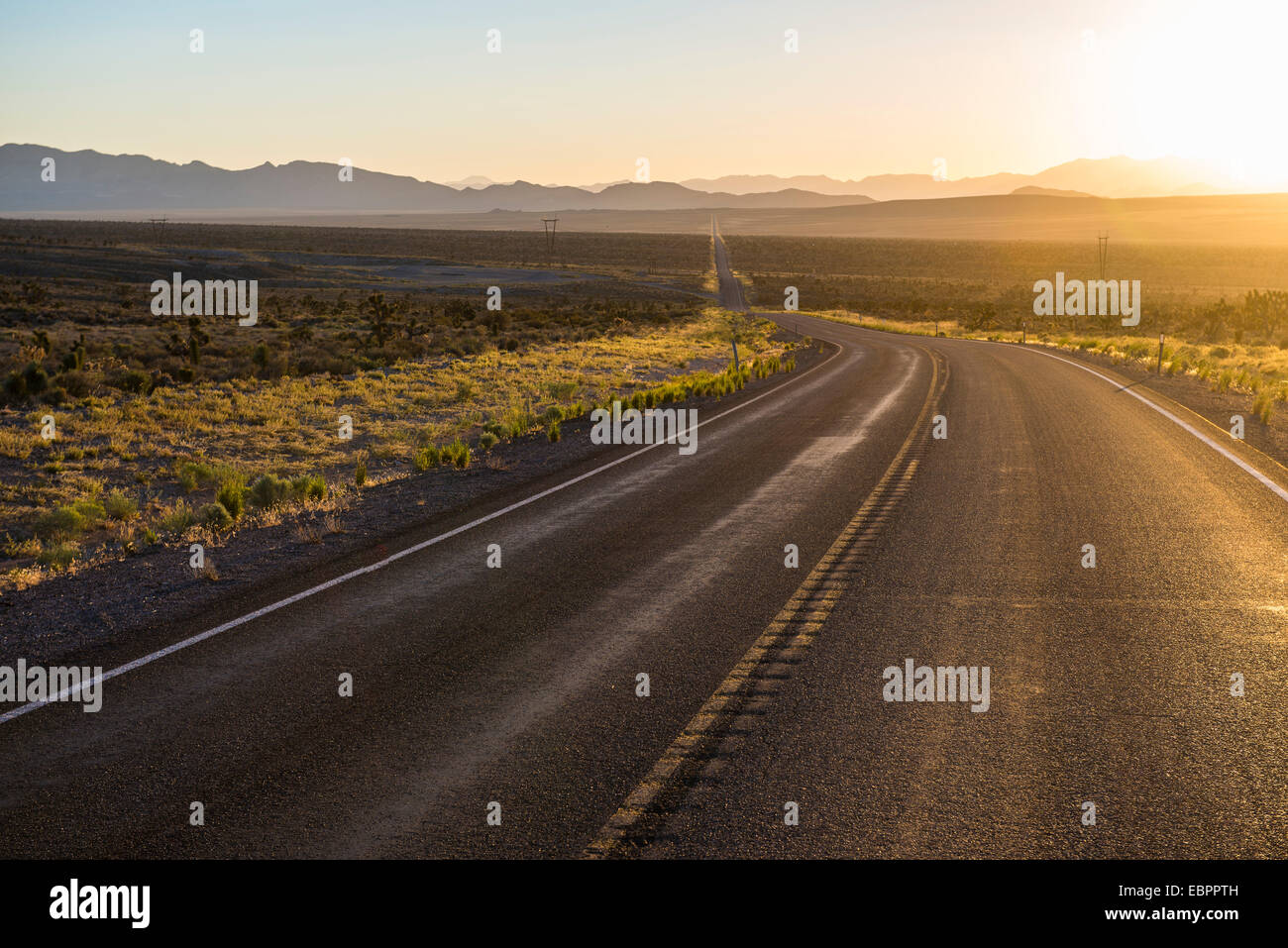 Lunga strada tortuosa al tramonto nella parte orientale del Nevada, Stati Uniti d'America, America del Nord Immagini Stock