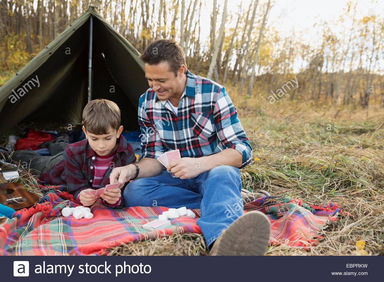 Padre e figlio carte da gioco al di fuori di tenda Immagini Stock