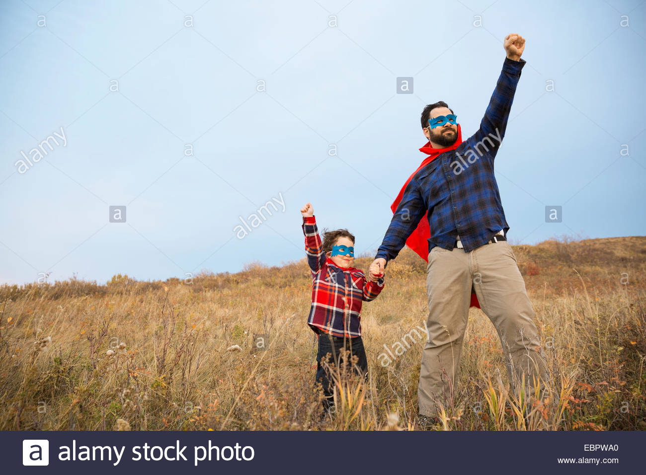 Padre e figlio in supereroe capes nel campo Immagini Stock
