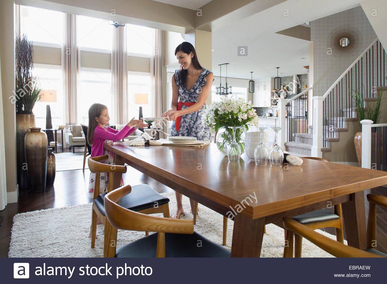 Madre e figlia nella tabella di impostazione in sala da pranzo Immagini Stock