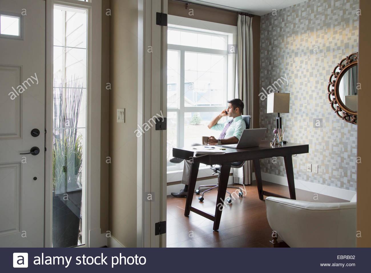 L'uomo parlando al cellulare in home office Immagini Stock