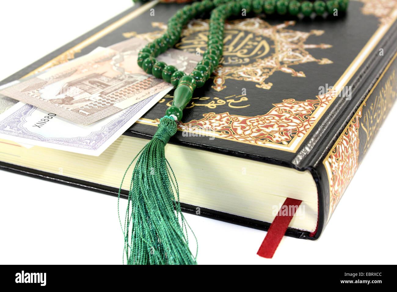 Sbattuto Corano con rupie pakistane prima di sfondo luminoso Immagini Stock