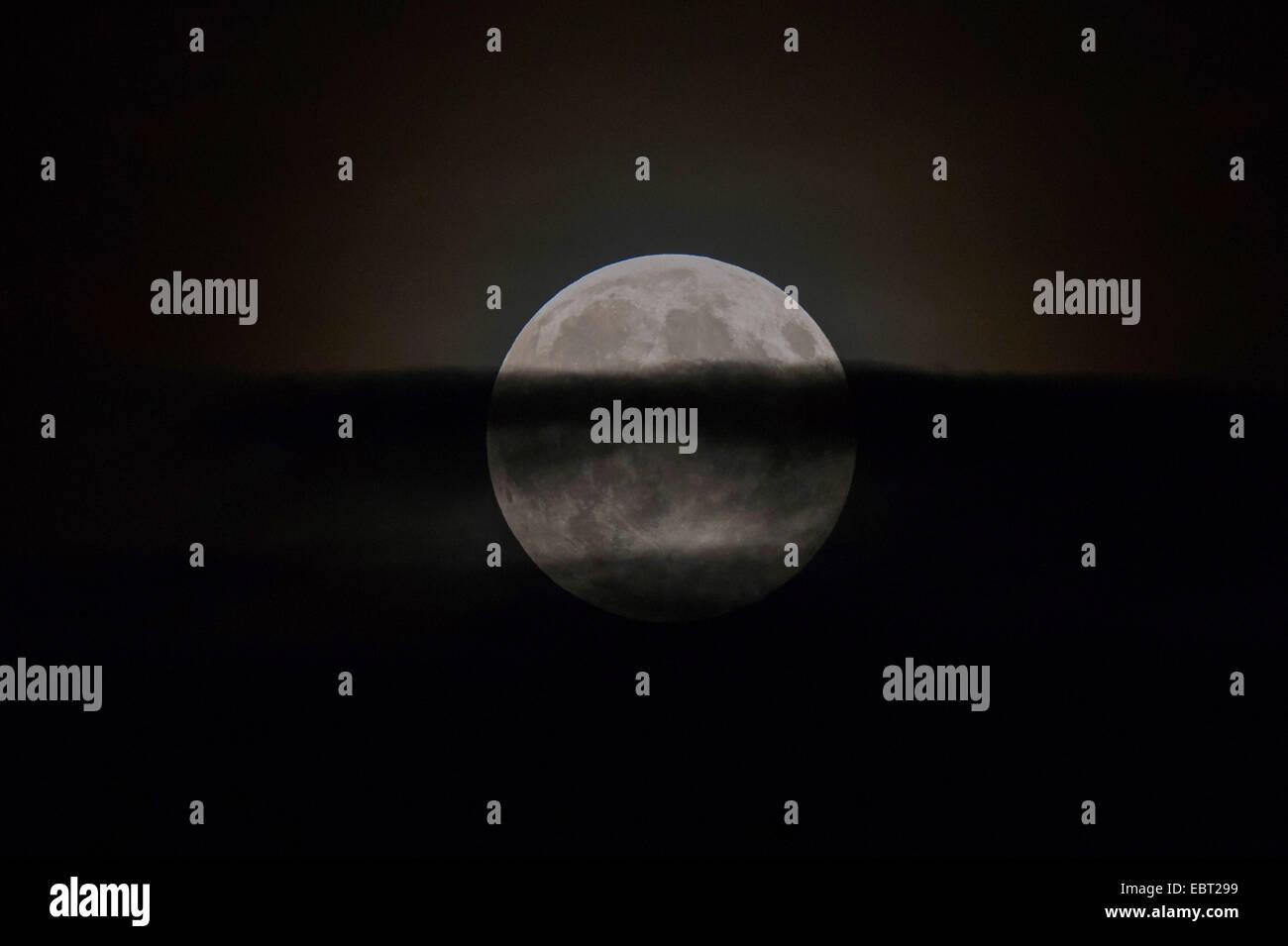 Luna piena, parzialmente oscurata attraverso il velo di nuvole, in Germania, in Baviera Immagini Stock