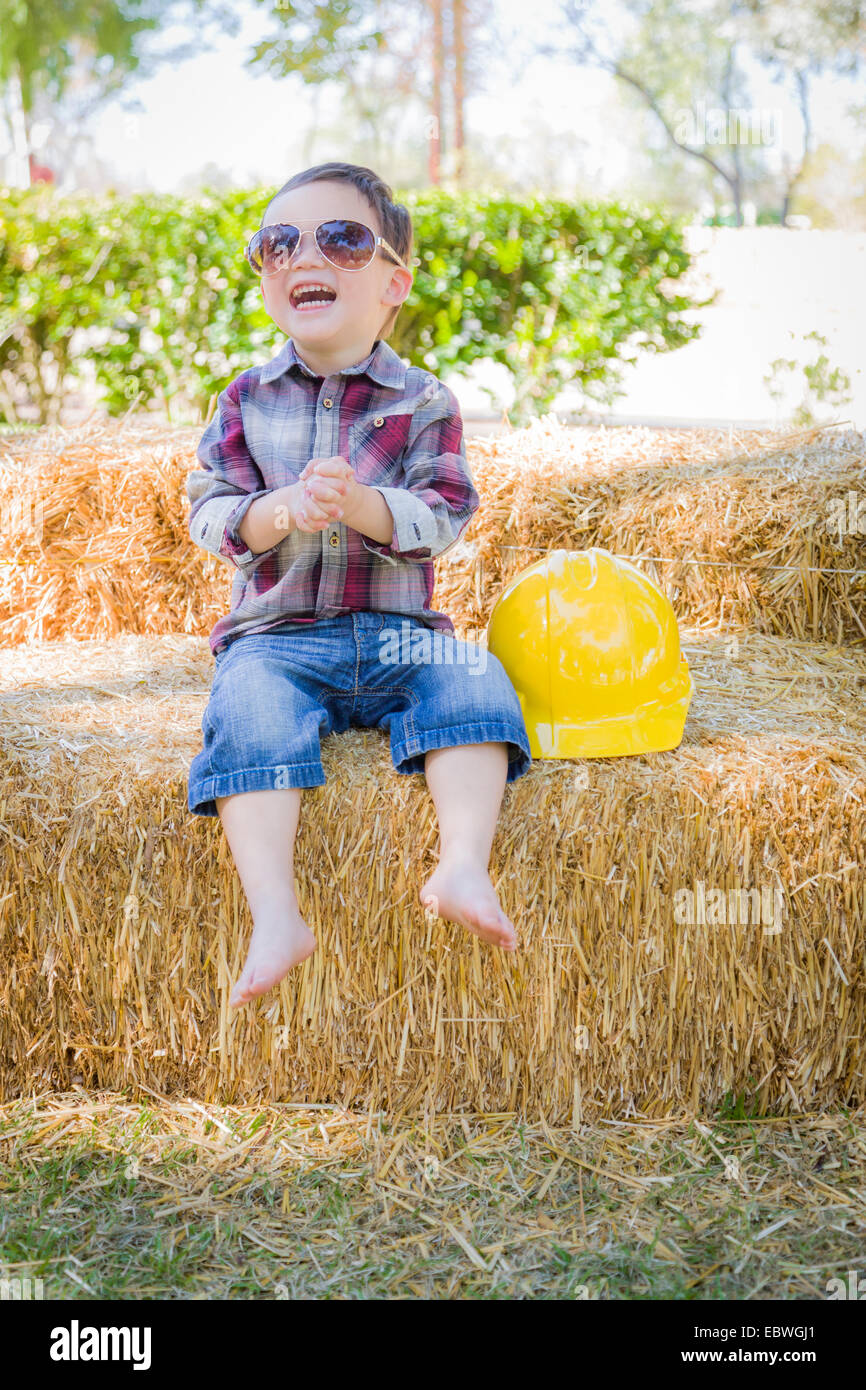 Carino giovane razza mista Boy a ridere con occhiali da sole e cappello rigido al di fuori seduta sulla balla di Immagini Stock