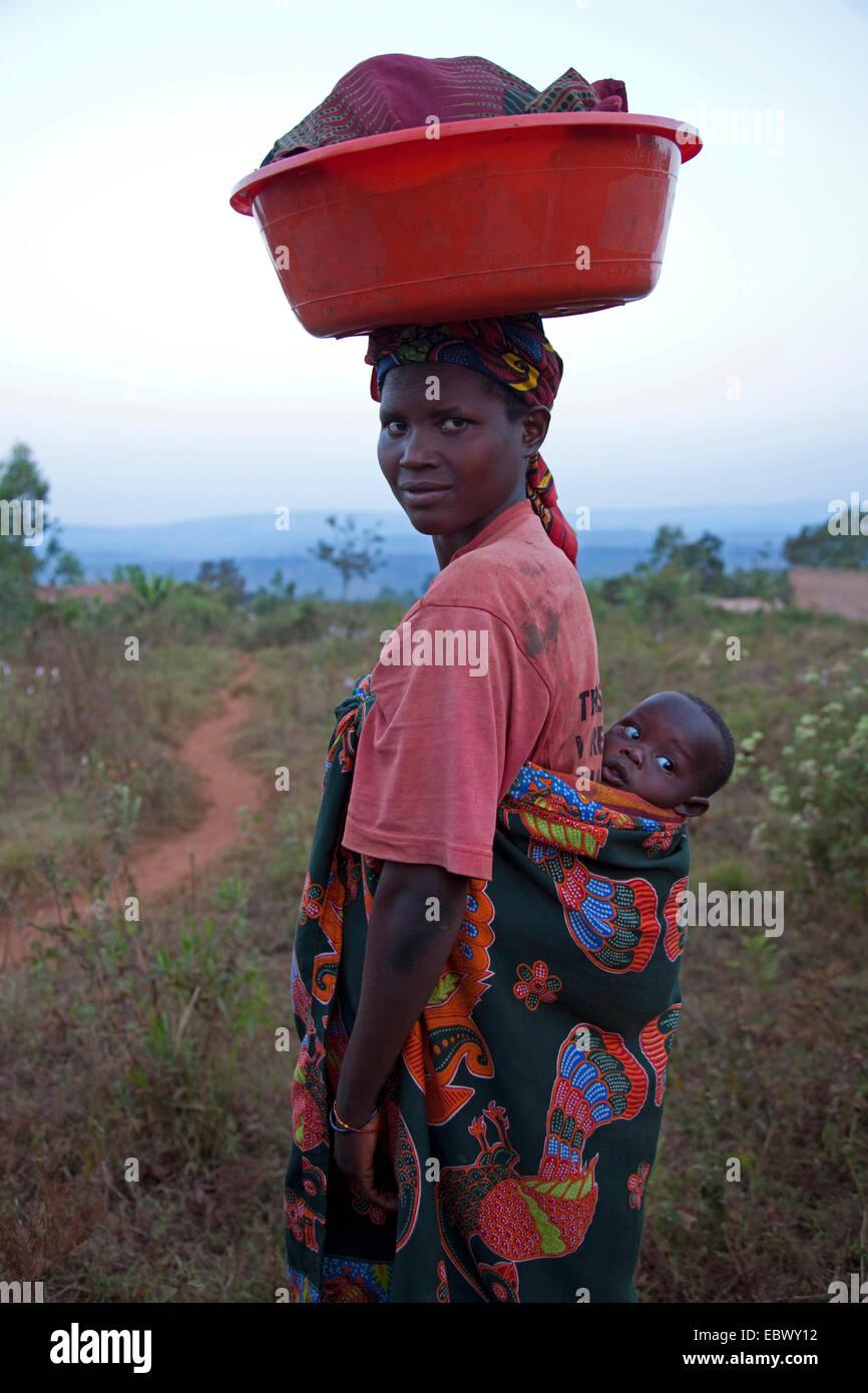Madre con bambino sulla schiena il trasporto di piatto sul suo capo, Burundi, Karuzi, Buhiga Immagini Stock