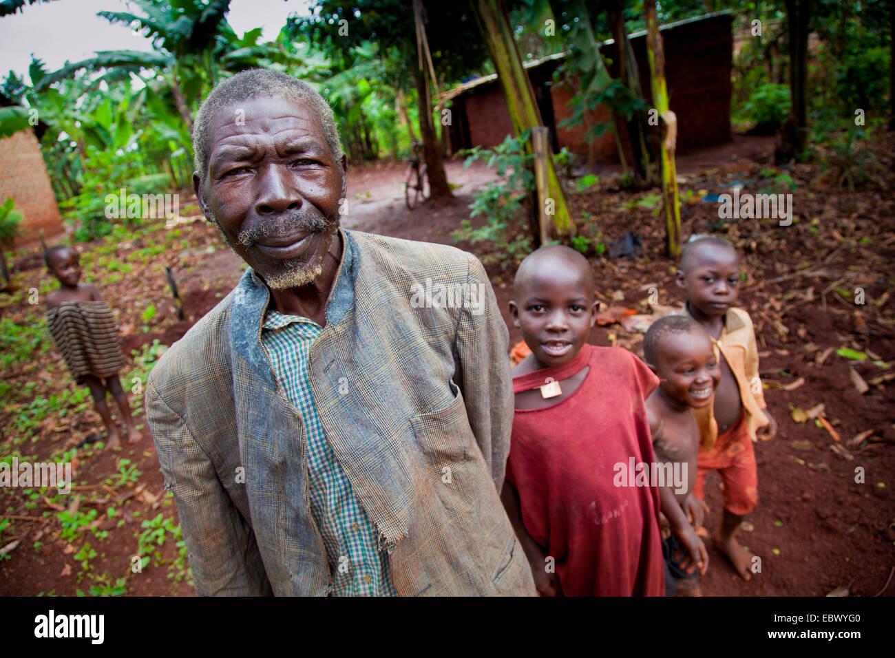 Nonno con una camicia strappata è in piedi con il suo grand bambini davanti al suo semplice casa di fango, Immagini Stock