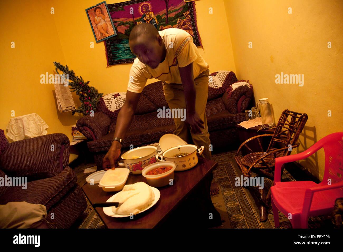 Uomo di mettere il cibo sulla tavola in una famiglia cristiana, Christian brodery sulla parete in background, Ruanda, Immagini Stock