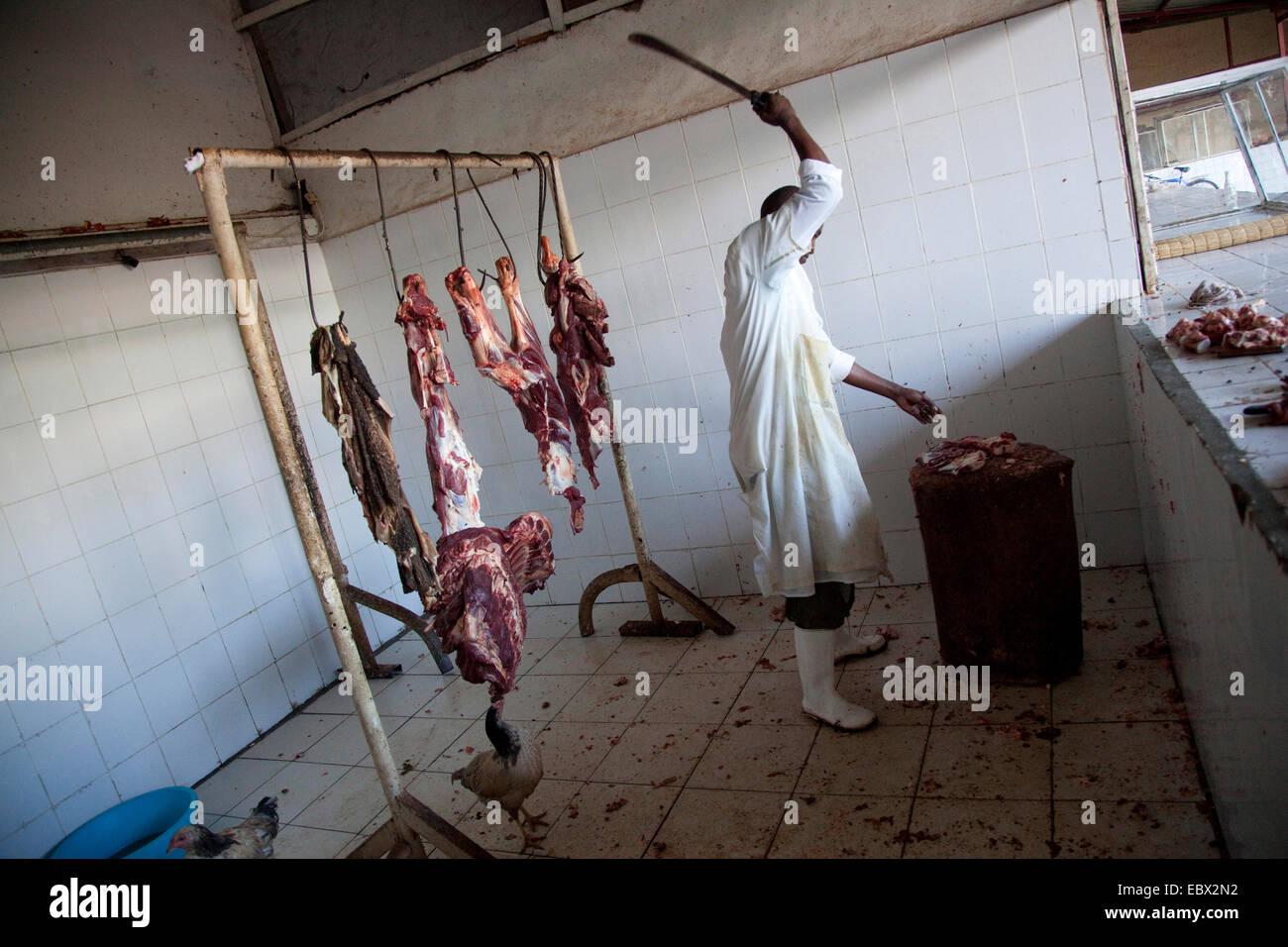 Butcher il taglio di carne su un tronco di legno, Ruanda, Nyamirambo, Kigali Immagini Stock