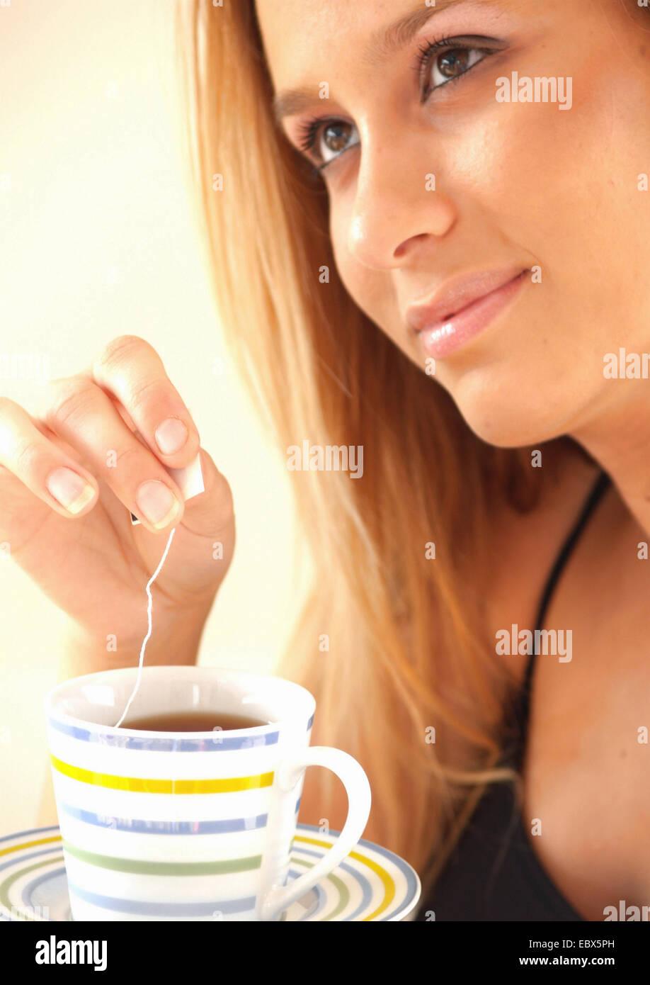 Giovane donna irradia serenità è immergendo un sacchetto da tè in una tazza Immagini Stock
