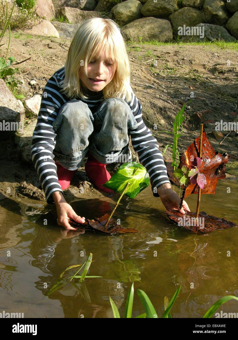 Bambino a un torrente di mettere due navi di corteccia in acqua Immagini Stock