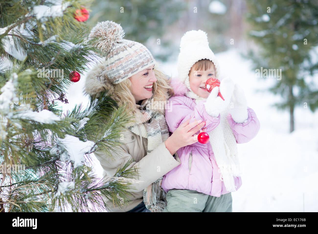 Felice genitore e bambino gioca con decorazioni natalizie per esterno Immagini Stock