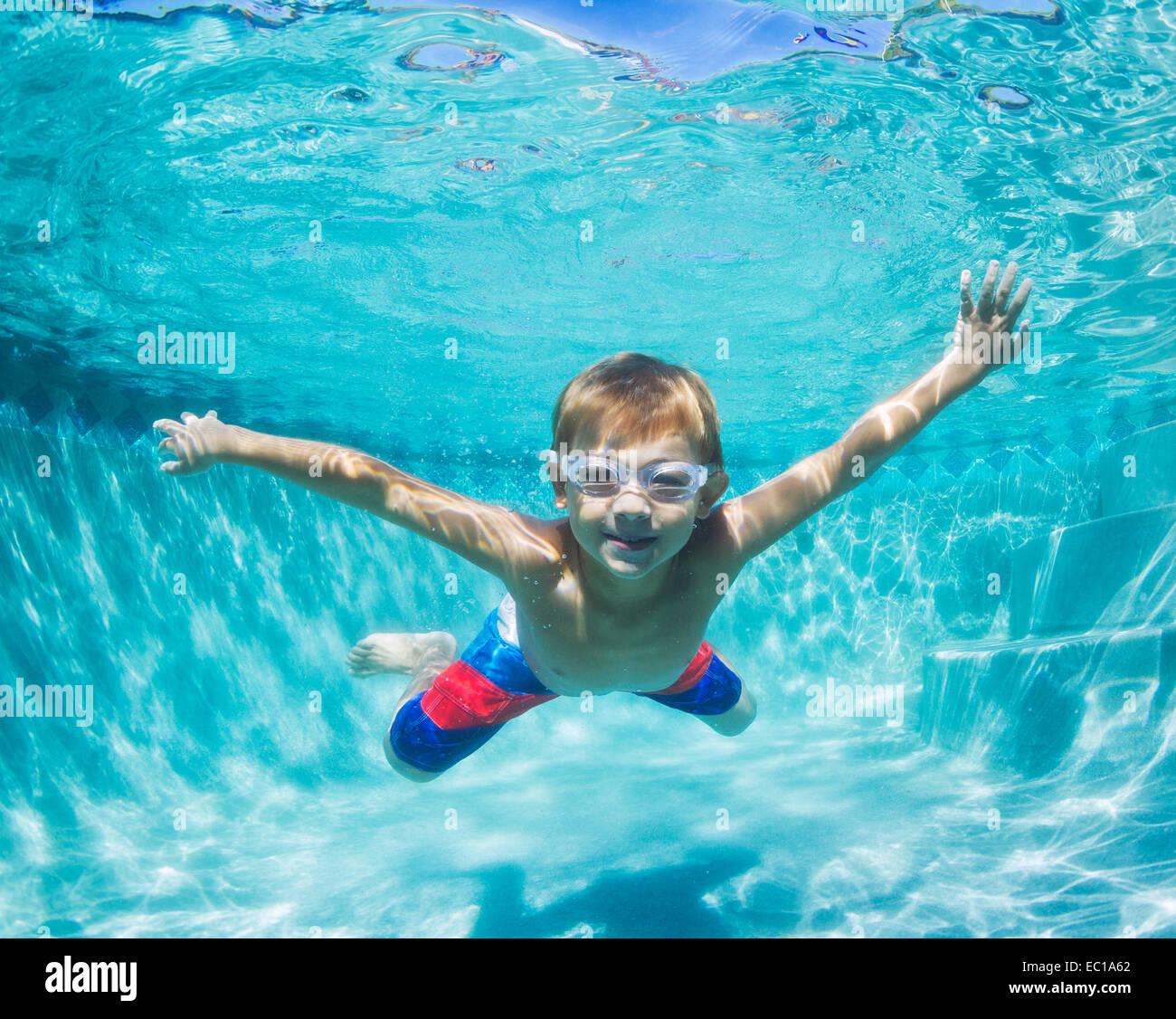 Underwater giovane ragazzo divertente in piscina con gli occhiali. La vacanza estiva di divertimento. Foto Stock