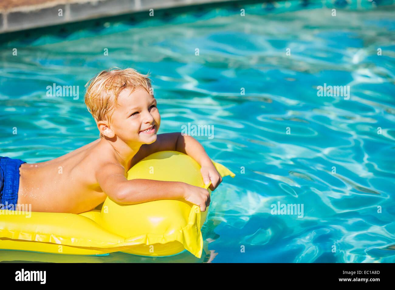 Giovane ragazzo in relax e divertimento in piscina sulla zattera di giallo. La vacanza estiva di divertimento. Stile Immagini Stock