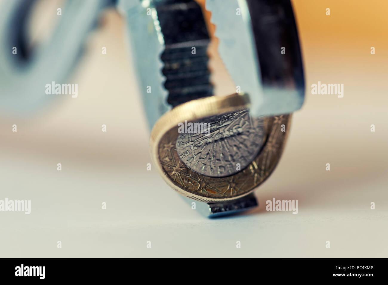 Un euro piegata tra le ganasce delle pinze con la curvatura concava Immagini Stock