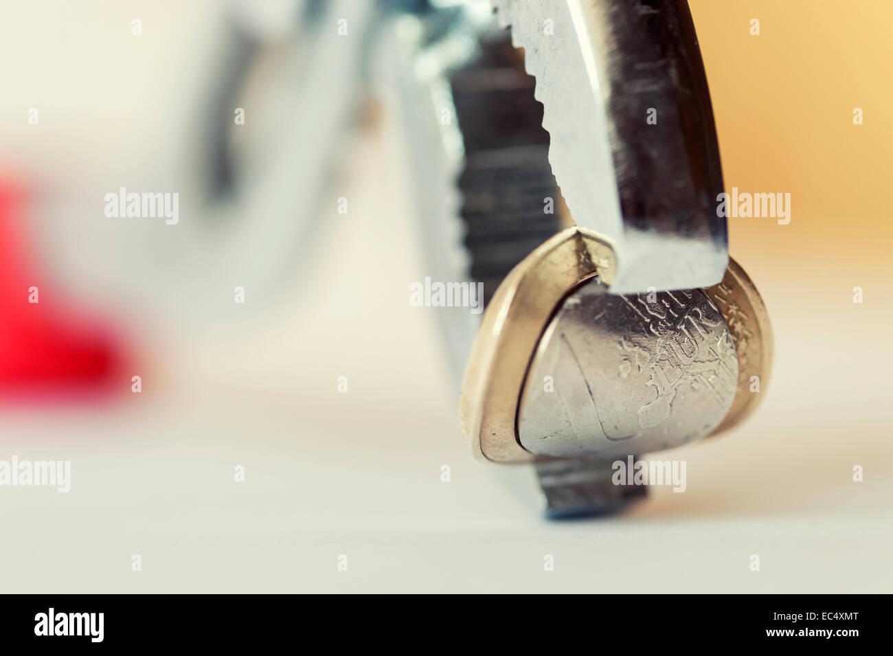 Un euro piegata tra le ganasce di una morsa con una curvatura convessa Immagini Stock