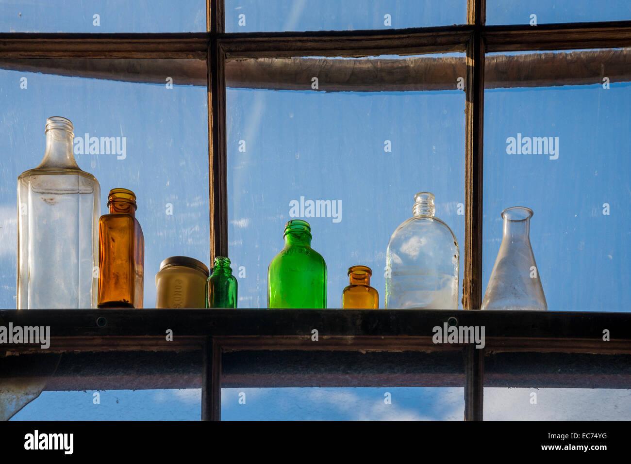 Vecchie bottiglie di vetro nella finestra Immagini Stock