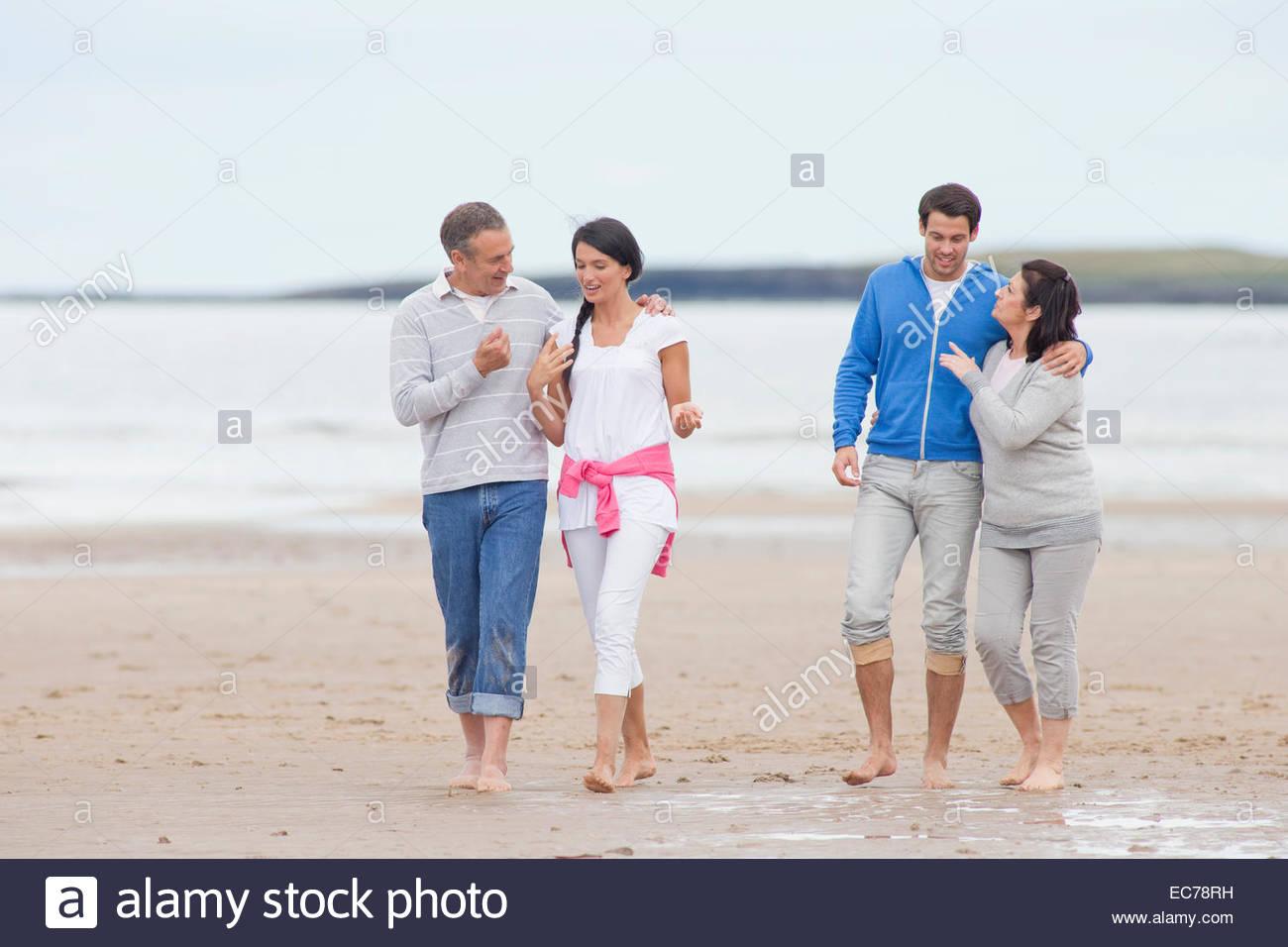 Ai genitori e ai figli maggiorenni a camminare insieme sulla spiaggia Immagini Stock