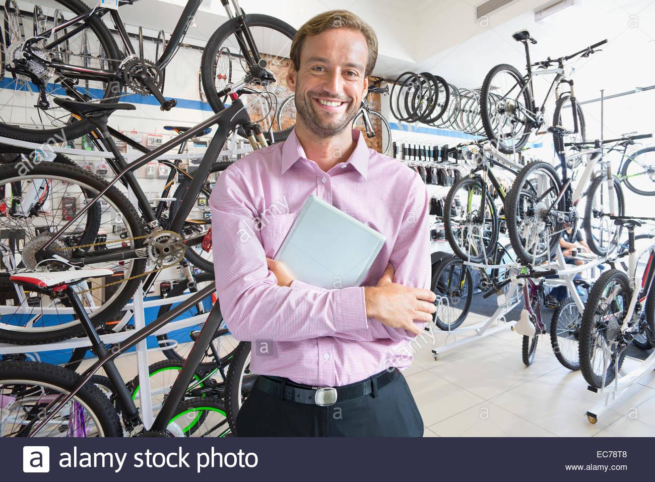 Il proprietario del negozio nel negozio di biciclette sorridente in telecamera Immagini Stock