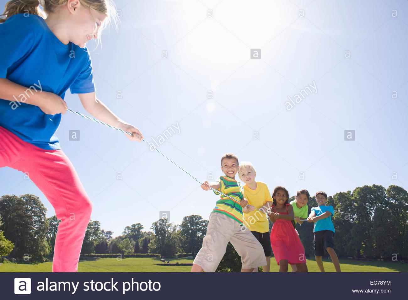Un gruppo di bambini che giocano rimorchiatore di guerra nel parco Immagini Stock