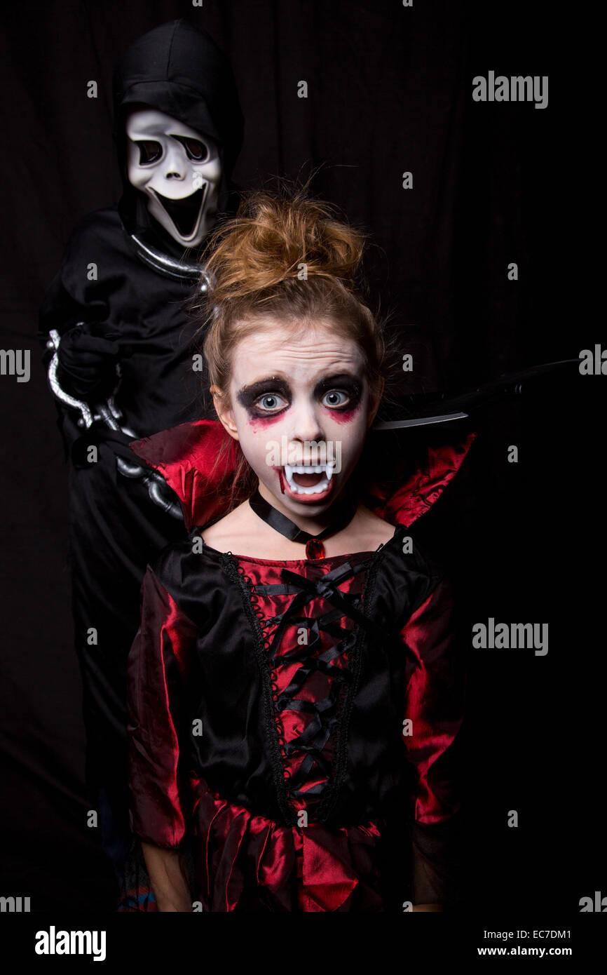 Ragazza masquarade come vampiro e ragazzo che indossa la maschera di Scream Immagini Stock