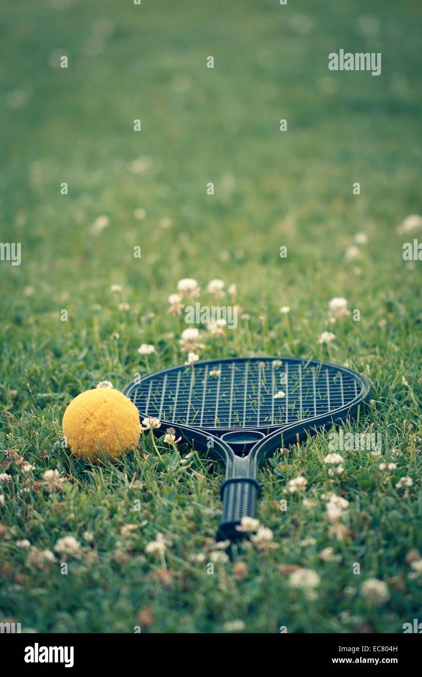 Plastica racchetta da tennis, palla gialla sull'erba Immagini Stock