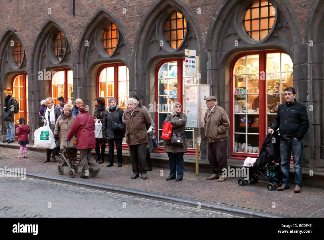 Il popolo belga sta in piedi in una coda di bus, - esempio della normale vita quotidiana; Bruges, Belgio, Europa Foto Stock
