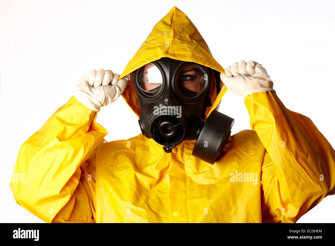 Donna che indossa indumenti protettivi e maschera a gas una protezione per il viso e guanti di gomma Immagini Stock