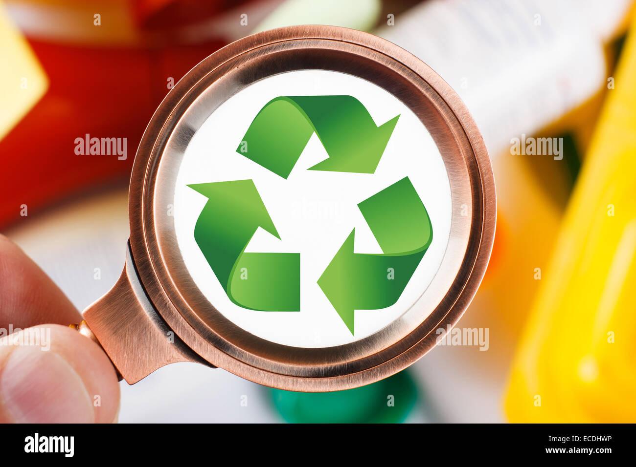 Gli uomini alla ricerca di un simbolo di riciclaggio su immondizia di plastica Immagini Stock