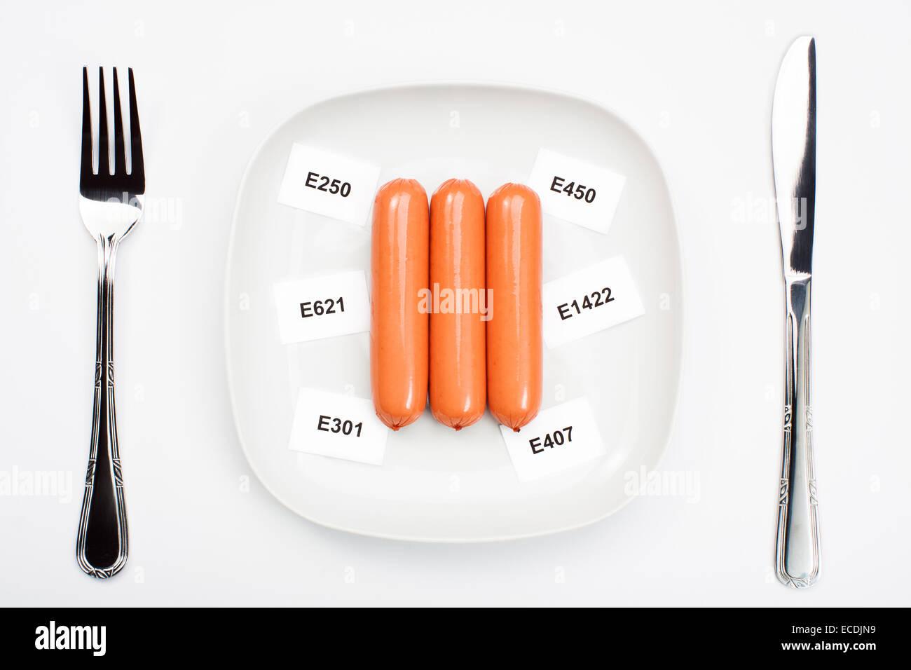 Cibo malsano concetto - additivi chimici nei prodotti alimentari. Salsicce su piastra Immagini Stock