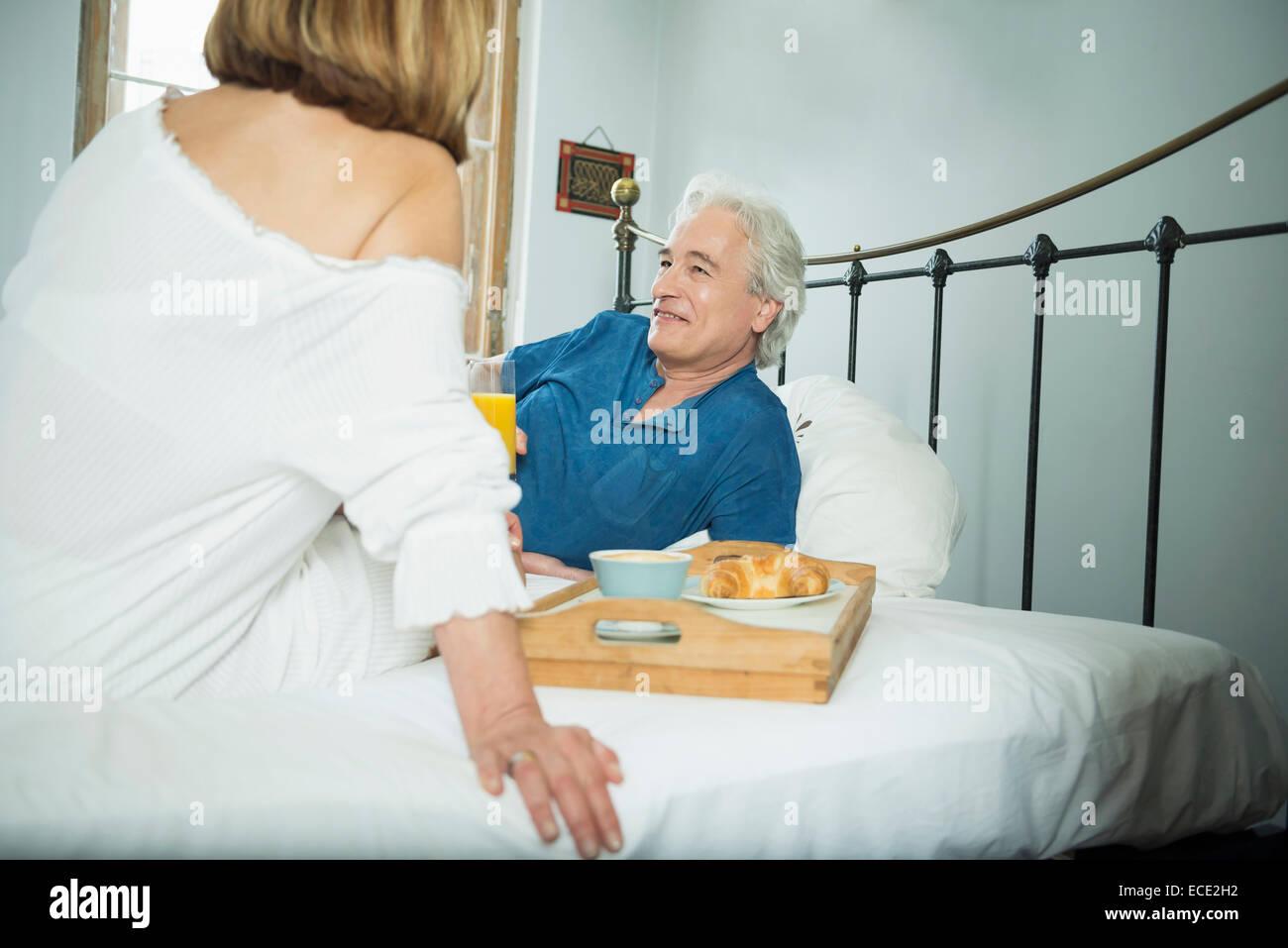 Giovane avente la colazione a letto, sorridente Immagini Stock