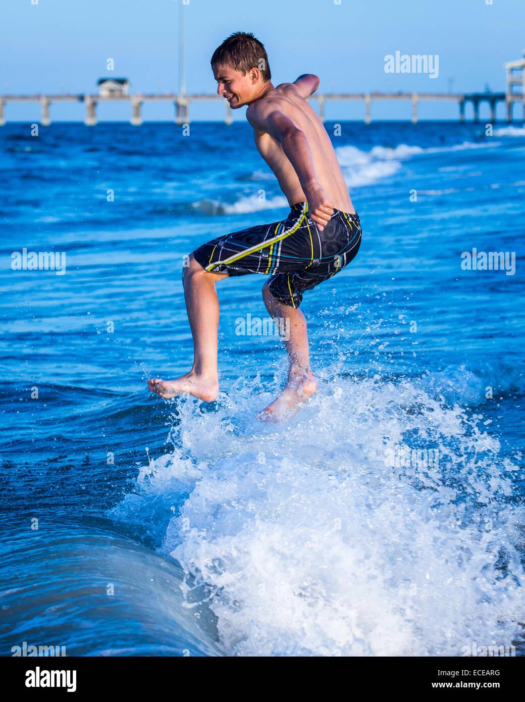 Boy jumping nell'oceano surf Immagini Stock