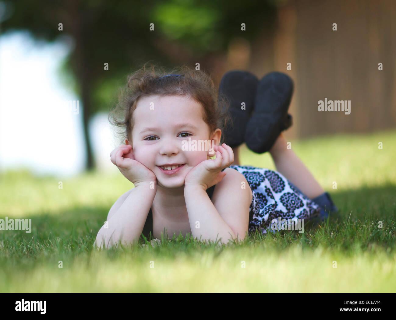 Felice ragazza (4-5) in posa sull'erba Immagini Stock