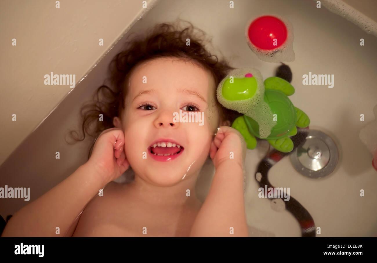 Il Toddler girl (2-3) con capelli ricci in vasca da bagno Immagini Stock