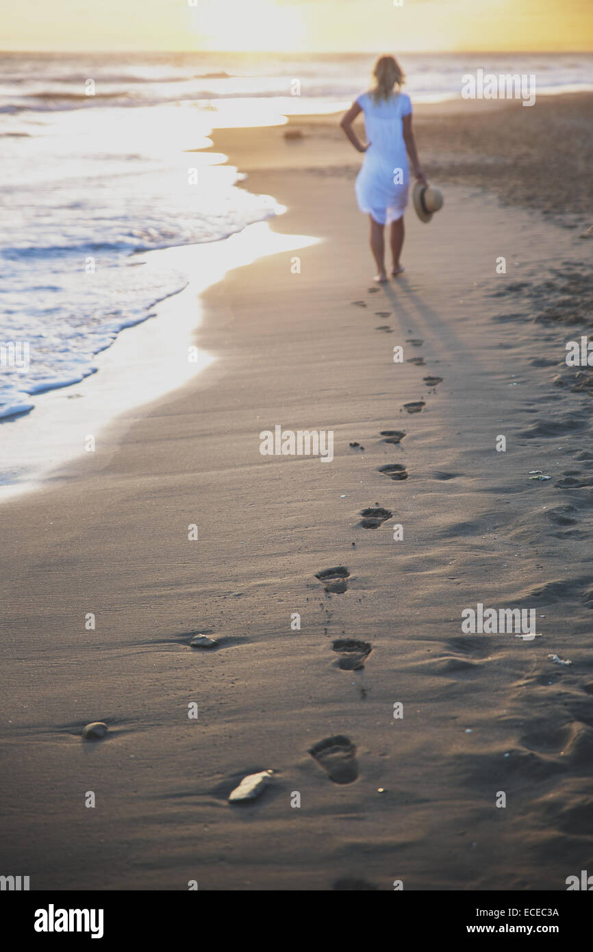 Bella donna di camminare sulla spiaggia con il suo orme indietro Immagini Stock