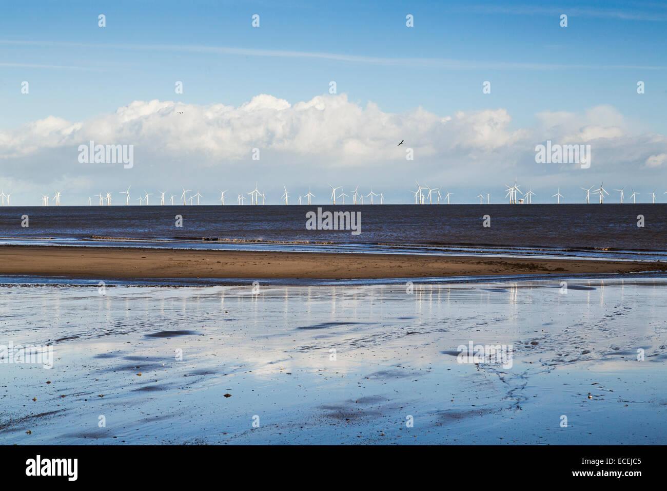 Una wind farm all'orizzonte alla stazione balneare di Skegness, Regno Unito Immagini Stock