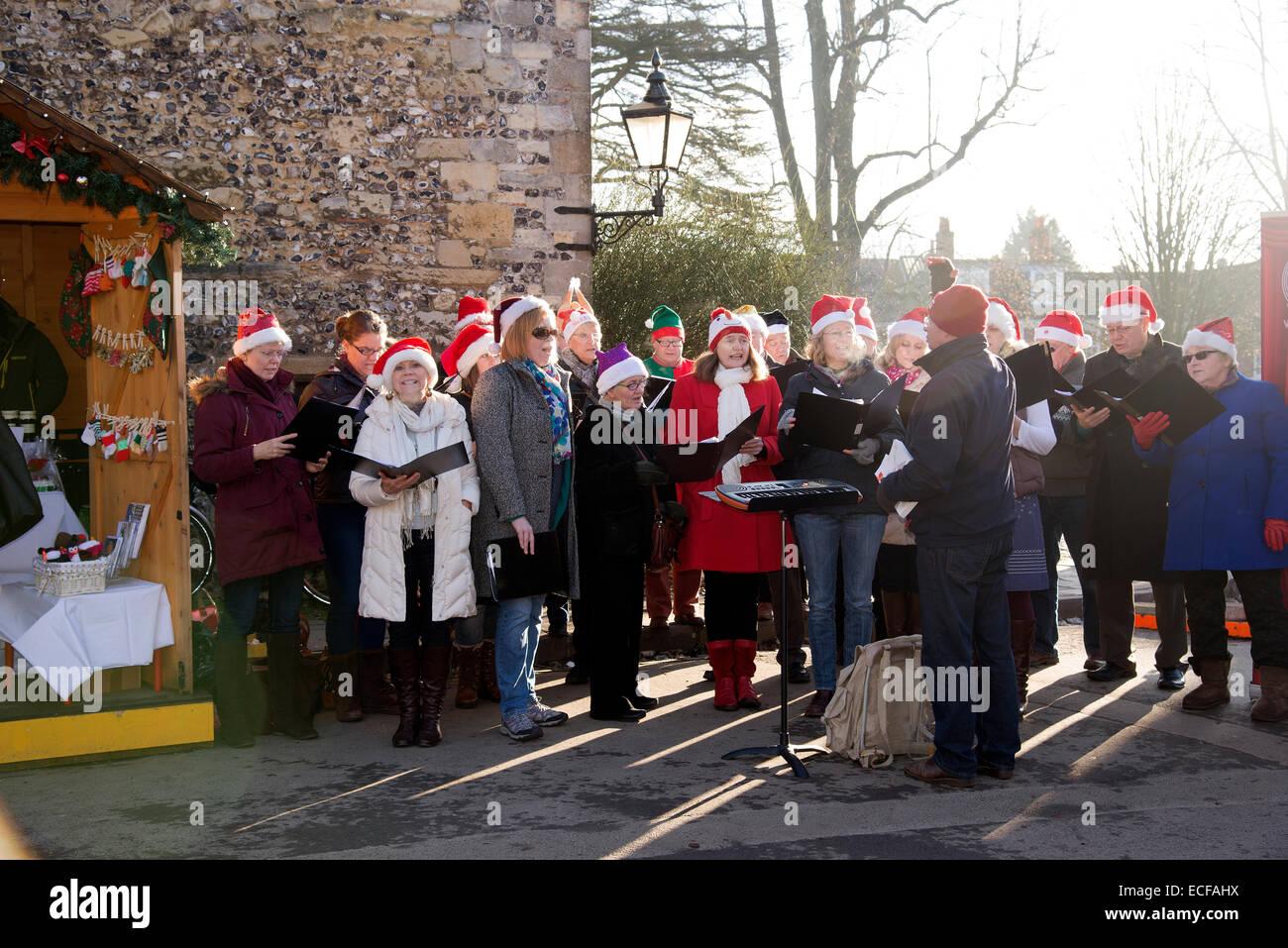 Carol cantanti di eseguire nel vicino la Cattedrale di Winchester Hampshire REGNO UNITO a cantare i canti natalizi Immagini Stock