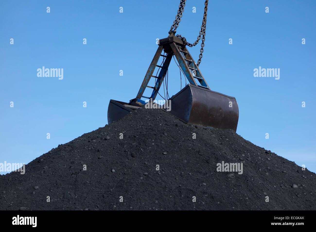 La parte superiore di un enorme mucchio di carbone con benna benna Immagini Stock