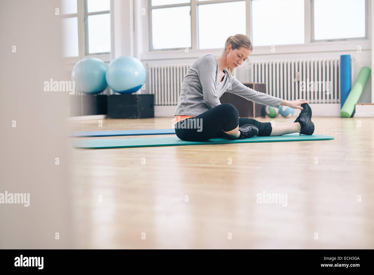 Colpo di una donna attraente seduta sul pavimento facendo esercizio. Montare donna seduta su esercizio mate facendo Foto Stock