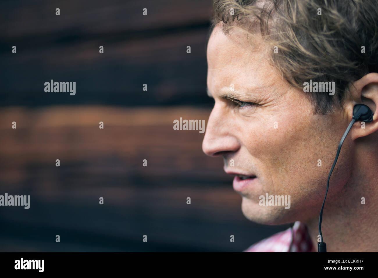 Uomo che indossa un dispositivo vivavoce esterno log cabin Immagini Stock