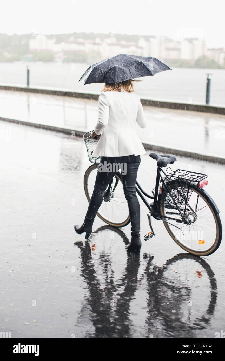 Lunghezza piena vista posteriore di imprenditrice camminando con la bicicletta su una strada di città durante Immagini Stock