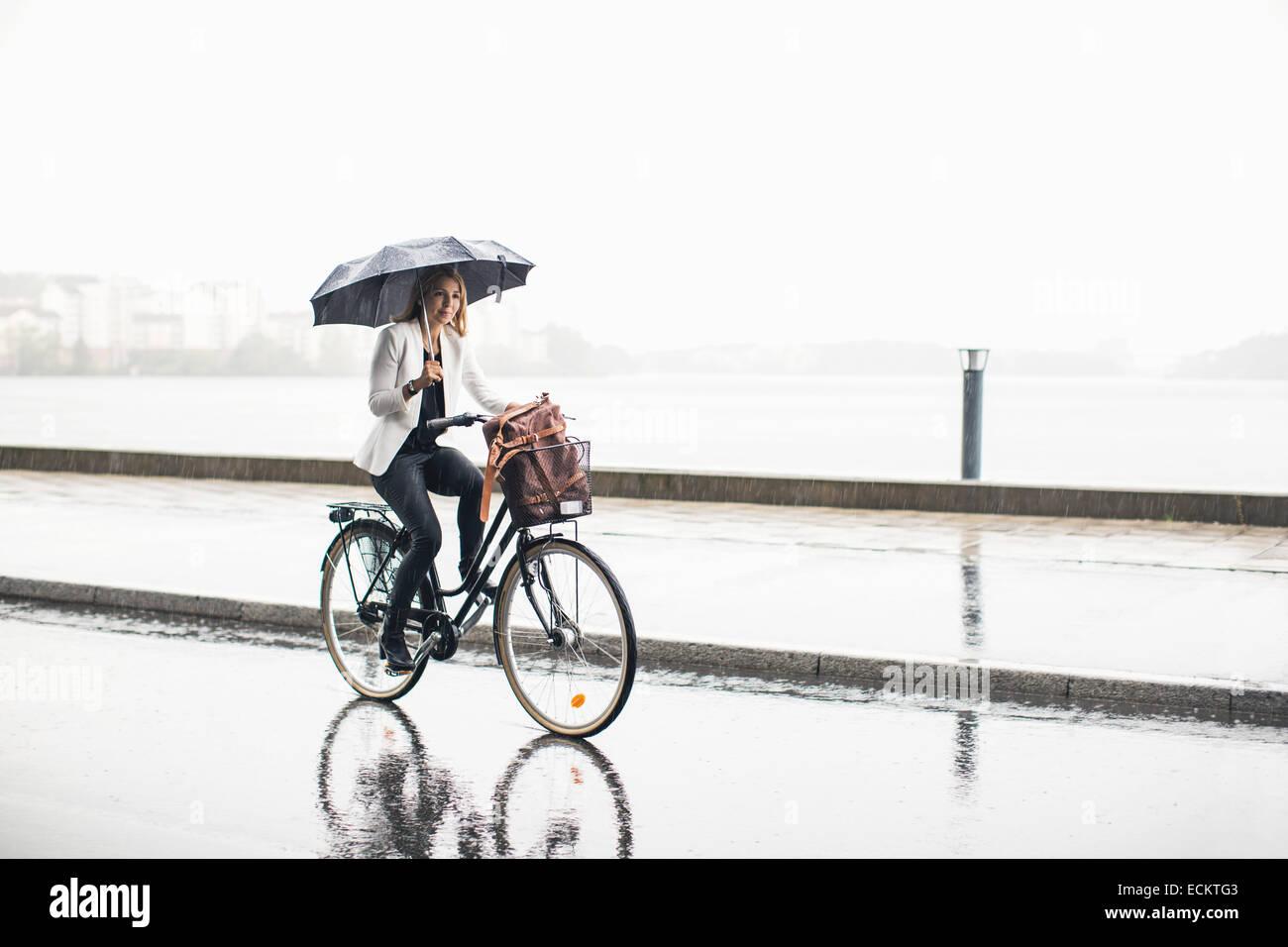 Lunghezza completa di imprenditrice Bicicletta Equitazione su bagnato via della città durante la stagione delle Immagini Stock