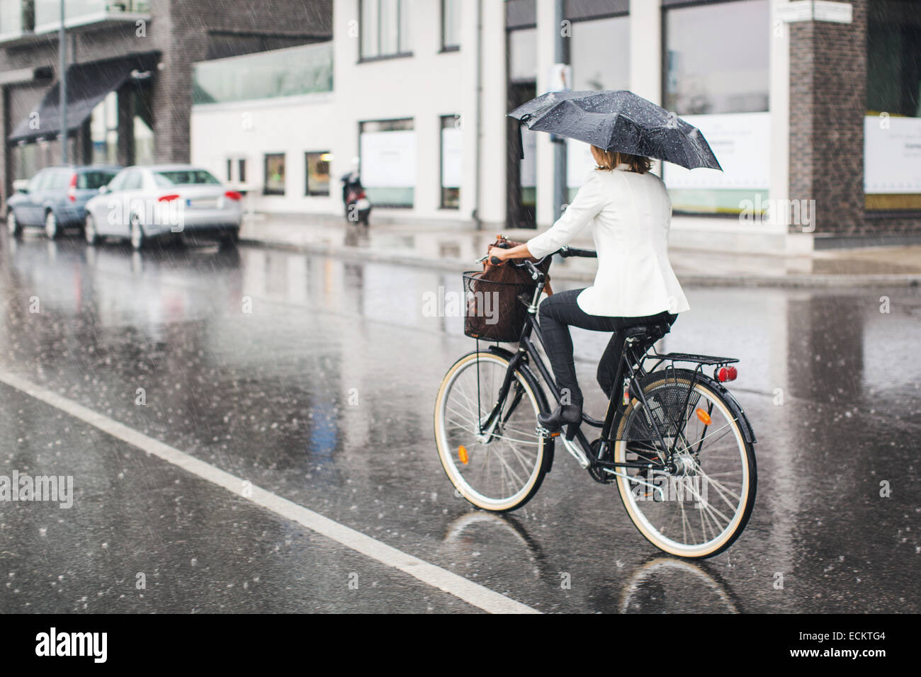 Lunghezza piena vista posteriore di imprenditrice Bicicletta Equitazione su bagnato via della città durante Immagini Stock