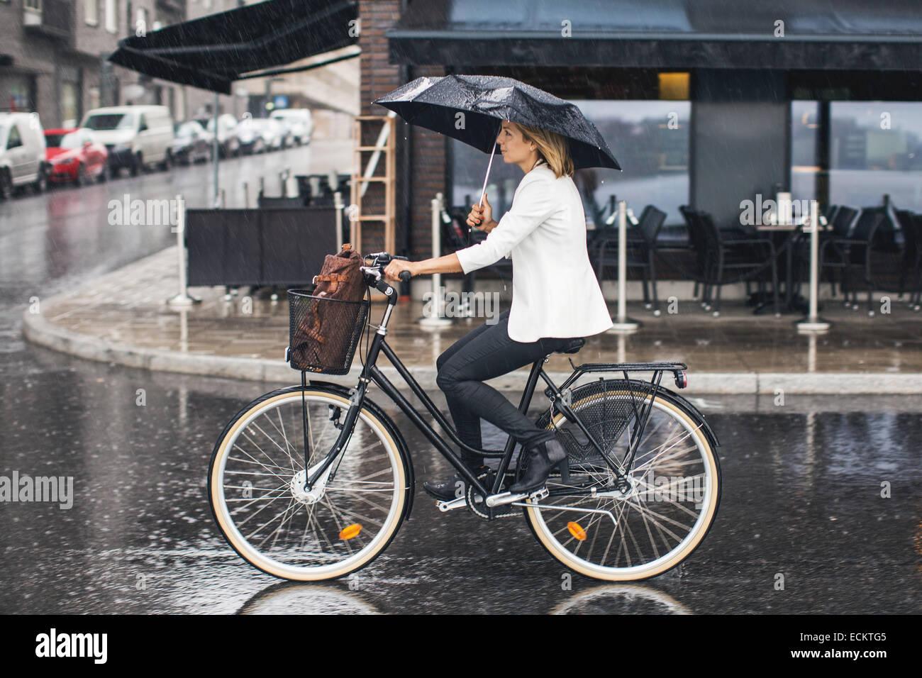 Imprenditrice Bicicletta Equitazione su bagnato via della città durante la stagione delle piogge Immagini Stock