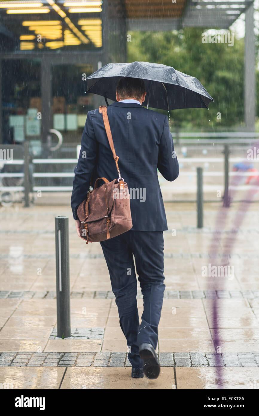 Lunghezza piena vista posteriore di imprenditore camminando sul marciapiede durante la stagione delle piogge Immagini Stock