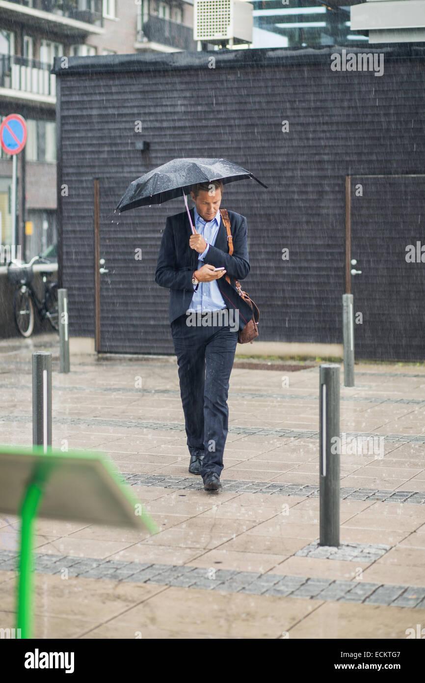 Lunghezza completa di imprenditore camminando sul marciapiede durante la stagione delle piogge Immagini Stock